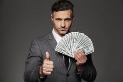 Foto del hombre rico 30s en el traje de negocios que sostiene la fan del dinero del efectivo foto de archivo libre de regalías