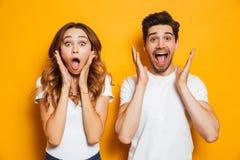 Foto del hombre y de la mujer emocionados de los pares en el grito básico de la ropa imagen de archivo