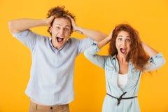 Foto del hombre y de la mujer emocionados 20s de los pares en scre básico de la ropa imagen de archivo