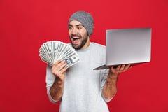 Foto del individuo feliz que sostiene el dinero del efectivo y el ordenador portátil de plata aislados sobre fondo rojo fotos de archivo libres de regalías