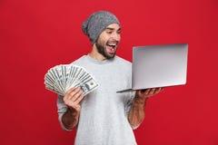 Foto del individuo rico que sostiene el dinero del efectivo y el ordenador portátil de plata aislados sobre fondo rojo foto de archivo