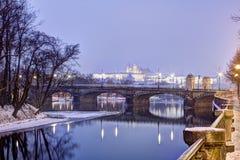 Foto del invierno de HDR de árboles en el banco de un río, de un puente y del castillo de Praga en el fondo fotografía de archivo libre de regalías