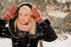 Foto del invierno de un rubio hermoso en manoplas rojas fotografía de archivo