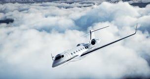 Foto del jet privado del diseño genérico de lujo blanco que vuela sobre la tierra Nubes blancas enormes en el fondo Recorrido de  imagen de archivo