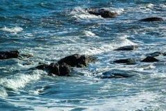 Foto del mar en el cual las ondas con las crestas blancas se rompen en las piedras fotos de archivo