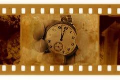 foto del marco de 35m m con el reloj de la vendimia Foto de archivo
