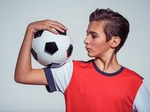 Foto del muchacho adolescente en la ropa de deportes que sostiene el balón de fútbol Fotografía de archivo