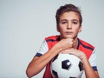 Foto del muchacho adolescente en la ropa de deportes que sostiene el balón de fútbol Fotos de archivo