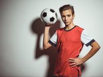 Foto del muchacho adolescente en la ropa de deportes que sostiene el balón de fútbol Fotos de archivo libres de regalías