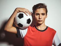 Foto del muchacho adolescente en la ropa de deportes que sostiene el balón de fútbol imagenes de archivo