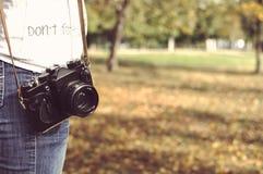 Foto del otoño con la muchacha que se coloca en un parque con la cámara Imagenes de archivo