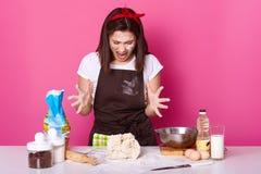 Foto del panadero moreno enojado que está enfermo y cansado de la pasta de amasamiento, vestido en camiseta casual y el delantal  foto de archivo