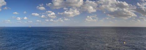 Foto del panorama de HDR de la última hora de la tarde del mar que atraviesa hasta el final al horizonte y al cielo nublado azul Imagen de archivo