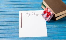 Foto del papel mi historia, regalo lindo y pila de libros en el wond Foto de archivo