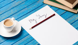 Foto del papel mi historia, taza de café y pila de libros en Imagen de archivo