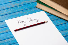 Foto del papel mi historia y pila de libros en el azul maravilloso Foto de archivo