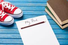Foto del papel mi libro, pila de libros y gumshoes rojos en el wo Foto de archivo libre de regalías
