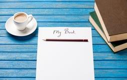 Foto del papel mi libro, pila de libros y taza de café en el w Fotos de archivo