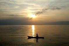 Foto del pescador y de la salida del sol en el lago Toba Fotos de archivo