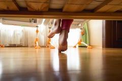 Foto del primer de debajo la cama de los pies descalzos de las muchachas en dormitorio con el piso de madera Imagenes de archivo