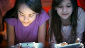 Foto del primer de dos adolescentes que mienten en piso y que usan los teléfonos móviles en la noche Foto de archivo libre de regalías