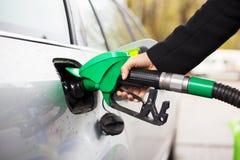 Foto del primer de la mano que sostiene el surtidor de gasolina y que rellena el coche en la gasolinera Foto de archivo libre de regalías