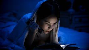 Foto del primer de la muchacha con el libro de lectura de la linterna Imagen de archivo libre de regalías