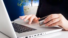 Foto del primer de la mujer joven que hace la tarjeta de crédito de las compras y de la tenencia del onkine fotografía de archivo libre de regalías