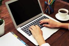 Foto del primer de las manos de los businesswomans usando el ordenador portátil Imagen de archivo