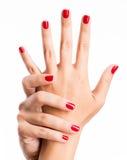 Foto del primer de las manos de una hembra con los clavos rojos Fotos de archivo