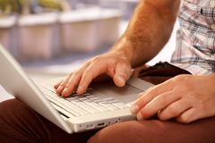 Foto del primer de las manos masculinas que mecanografían en el ordenador portátil Fotografía de archivo