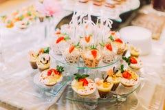 Foto del primer de los postres sabrosos adornados con las frutas en el sistema de la tabla de la boda Fotos de archivo