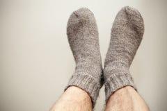 Foto del primer de pies y de calcetines de lana Imagenes de archivo
