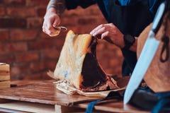 Foto del primer de un cocinero del cocinero que corta la carne desigual exclusiva en la tabla en una cocina con el interior del d fotos de archivo libres de regalías