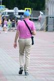 Foto del primer del hombre en la situación beige de la camiseta aislado en el fondo rosado que mira atento la pantalla del teléfo fotografía de archivo libre de regalías