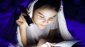 Foto del primer del libro de lectura del adolescente con la manta inferior con la linterna Imágenes de archivo libres de regalías