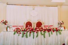 Foto del primer del sistema de la tabla de la boda adornado con las rosas rojas Estilo antiguo Fotos de archivo libres de regalías