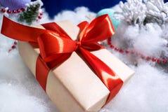 Foto del primo piano del contenitore di regalo con l'arco rosso su fondo blu e dell'imitazione della neve fotografia stock libera da diritti