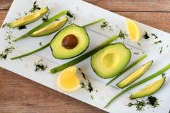 Foto del primo piano degli avocado affettati freschi, della cipolla fresca e dei pezzi di limone nel piatto di porcellana bianco  fotografie stock libere da diritti