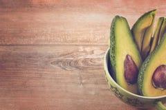 Foto del primo piano degli avocado affettati freschi, semi marroni visibili in ciotola verde su fondo di legno marrone Concetto v immagine stock