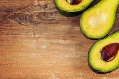 Foto del primo piano degli avocado affettati freschi, semi marroni visibili su fondo di legno marrone immagine stock libera da diritti