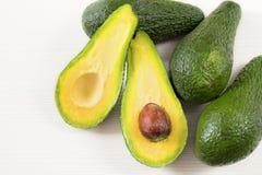 Foto del primo piano degli avocado tagliati alla metà, semi marroni visibili, con più avocado su fondo di legno bianco fotografie stock libere da diritti