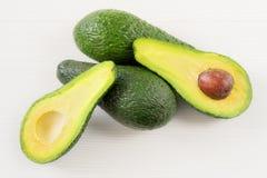 Foto del primo piano degli avocado tagliati alla met?, semi marroni visibili, con pi? avocado su fondo di legno bianco immagini stock libere da diritti