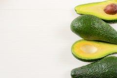 Foto del primo piano degli avocado tagliati alla met?, semi marroni visibili, con pi? avocado su fondo di legno bianco fotografia stock libera da diritti