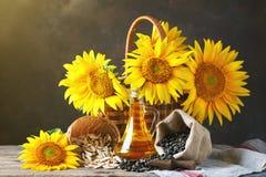 Foto del primo piano dei girasoli e dell'olio di girasole con i semi sopra su una tavola di legno Bio- e concetto organico del pr immagini stock libere da diritti