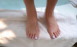 Foto del primo piano dei piedi del ` s della donna che stanno sull'asciugamano bianco fotografie stock libere da diritti