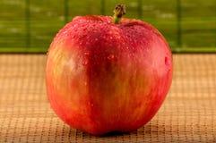 Foto del primo piano della mela rossa bagnata con le gocce di acqua su fondo di bambù vago immagini stock