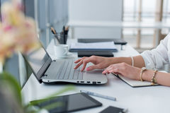 Foto del primo piano delle mani femminili con gli accessori che lavorano al computer portatile in un ufficio moderno, facendo uso fotografia stock libera da diritti