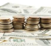 Foto del primo piano delle monete delle pile sopra i dollari Fotografia Stock