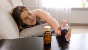 Foto del primo piano di giovane donna malata che si trova sul sofà e che raggiunge per le pillole sul comodino Immagini Stock